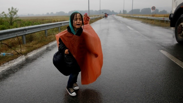 A Syrian refugee girl cries as she walks through a rainstorm towards Greece's border with Macedonia, near the Greek village of Idomeni, September 10, 2015. Most of the people flooding into Europe are refes fleeing violence and persecution in their home countries who have a legal right to seek asylum, the United Nations said on Tuesday. REUTERS/Yannis Behrakis  - RTSFW8